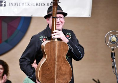 "Tim Grimm shows the back of his guitar, as described in the song ""13 Years."" Photo by John Cote"